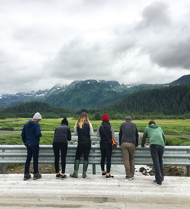 Familiary Tour participants looking over road into river in Alaska