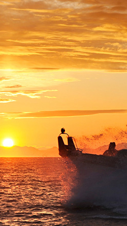 Boat crashing against waves in Alaska at sunset